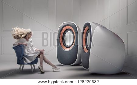 Young fashionable lady listening to big loudspeakers