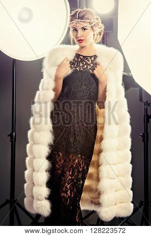 Stunning beauty model posing at studio in light flashes. Professional fashion model. Celebrity.