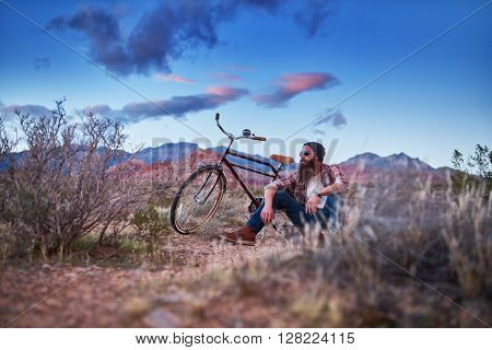 bearded guy with bike in desert