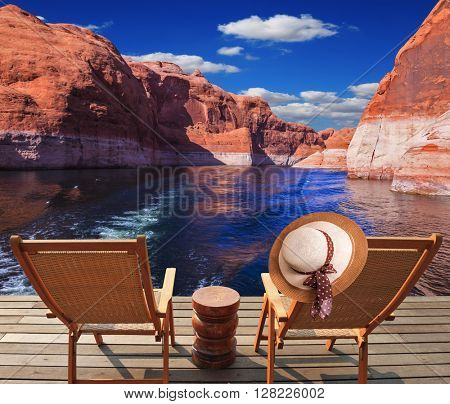 Waves from the boat dissect the lake Powell on the river Colorado. Aft vessels cost two chaise lounges. On a back of one the elegant straw women's hat hangs