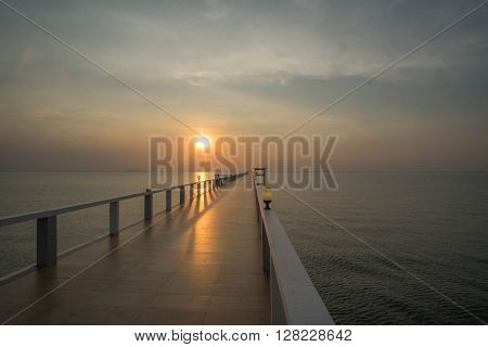 Beautiful sunset on beach and bridge in silhouette twilight golden hour/Sunset on beach and bridge silhouette