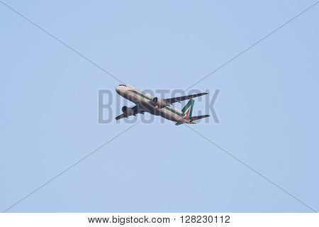 Torino Italy - April 18 2016: Alitalia domestic flight n. AZ1435 arriving at Torino International Airport from Rome Italy. Telephoto view from below of the flying Airbus 320 aircraft with clear sky.