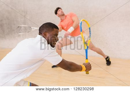 Two men playing match of squash. Back view of squash player in action reaching on squash court.