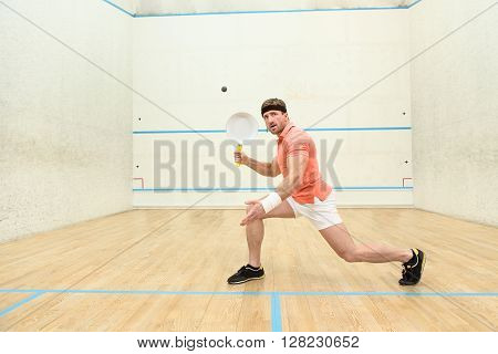Squash player hiting drop shot in squash court. Handsome man in orange t-shirt posing for photographer indoors while playing squash game.