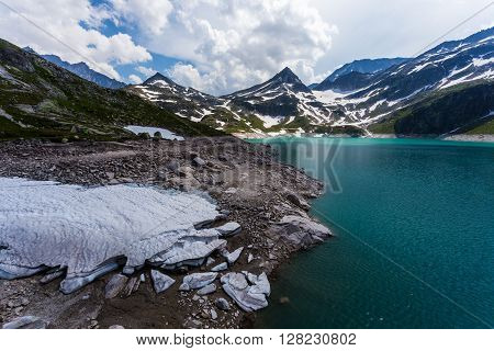 Weissee in Alps beautiful lake in Austrian mountains. Turquoise lake high in mountains. Frozen snow in foreground