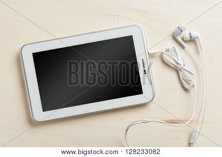 Small tablet pc with blank area on touchscreen and in ear headset on wood table