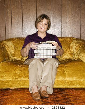 書籍のスタックを保持のリビング ルームのソファの上に座って白人中年の女性。