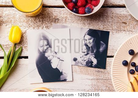Mothers day composition. Black-and-white pictures of mother holding her little baby daughter and a breakfast meal. Studio shot on wooden background.