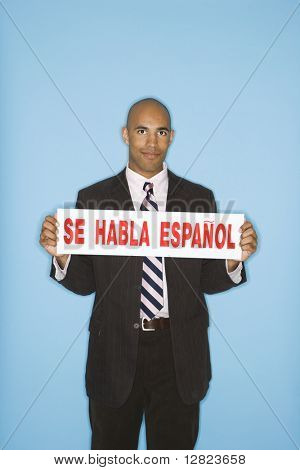 African American man holding sign reading se against blue background.