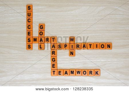 Letter spelling Success Smart Goal Target Aspiration Teamwork and Win on wooden background with copy space. Success business concept