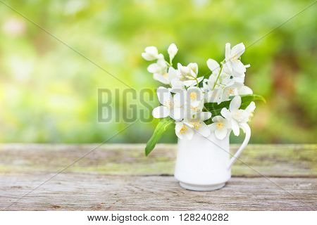 Delicate jasmine flowers in a small porcelain jug