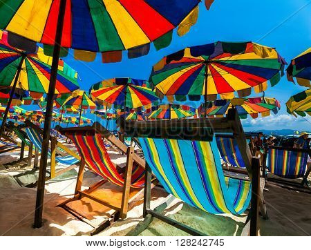 Beach with colourful sun loungers and parasols
