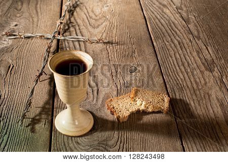 Chalice bread and cross on the wooden table