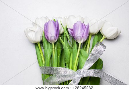 Bouquet of white and purple tulips with silver ribbon on a pearl white tile