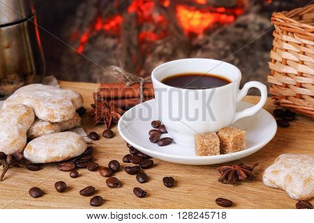 Cup of coffee with spices and cake in the background of a burning fireplace