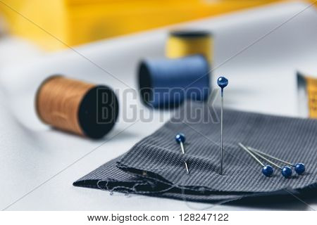 Sewing background. Accessories for needlework on white cloth background. Sewing push pin around sewing tools.