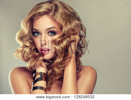 Beautiful girl with long wavy hair . Blonde model with curly hairstyle . jewelry bracelet