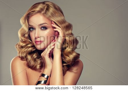 Beautiful girl with long wavy hair . Brunette with curly hairstyle . jewelry bracelet