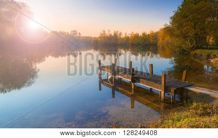 A wooden jetty juts out onto a calm lake with autumn coloured trees bordering the shores. The sun is setting behind the trees on the far bank