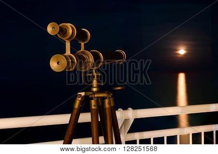 Telescope with amazing moonrising over the sea