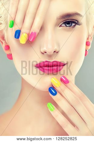 Beautiful girl  with colorful makeup and manicure nails . Stylish blonde girl with bright makeup and colorful nail Polish on  nails . Spring and summer look and Earrings beads
