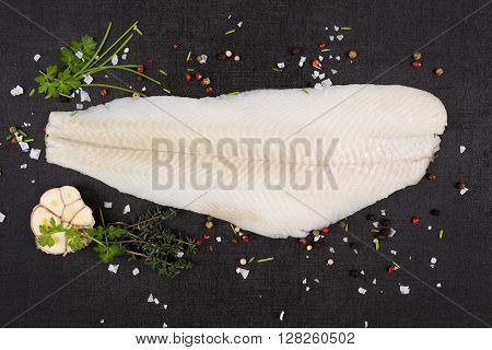 Fresh halibut fillet with fresh herbs and garlic on dark black stone background top view. Luxurious seafood eating background.