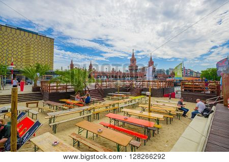 BERLIN, GERMANY - JUNE 06, 2015: Public and beautiful square where people can eat and talk, behind oberbaumbrucke,