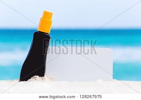 Blank White Board And Sunscreen Protection Cream On Sand