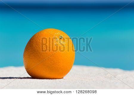 Orange Fruit On Sand Against Turquoise Caribbean Sea Water