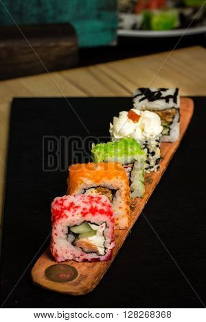 Sushi multicolored roll mix. Sushi assorti on yellow plate wooden board food photography