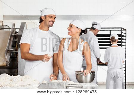 Baker's Looking At Each Other While Making Dough