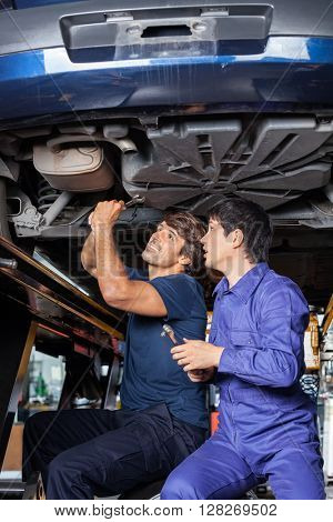 Mechanics Working Underneath Lifted Car