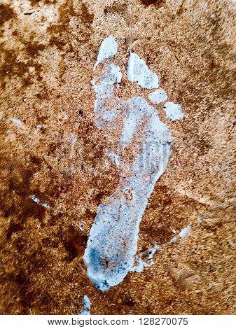 Grey paint foot print on a textured floor