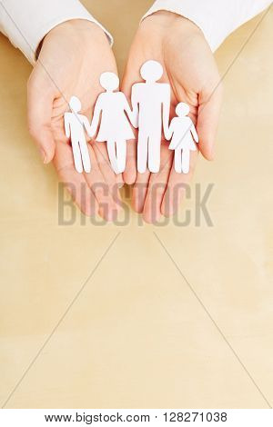 Two female hands holding a paper family sillhouette