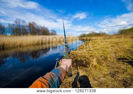 man fishing on the river in sunny day. Man hand keep fishing rod and catching. Process of fishing with view from eyes.