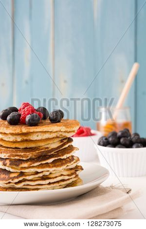 Pancakes with raspberries, blueberries and honey on bue wood background