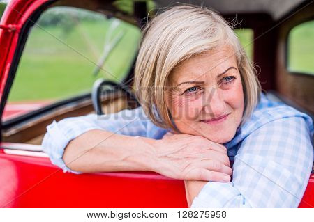 Close up of senior woman in checked blue shirt inside vintage pickup truck