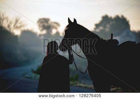 Silhouette of a girl in a raincoat kissing a horse on dark background with blue mist. The rider and the horse when it dawns.