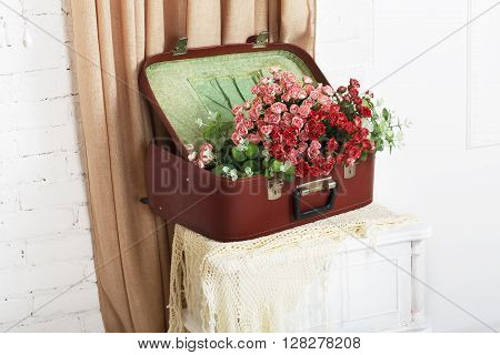 Shabby chic wedding. Wedding floral decor composition, flowers in vintage brown suitcase at bedside. Old suitcase with bouquet roses. Vintage, rustic, country decor. Floristic decoration. Flowerbed.