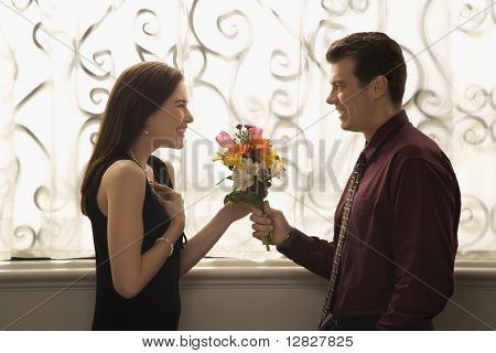 Mid adult Caucasian man presenting surprised woman with bouquet of flowers.