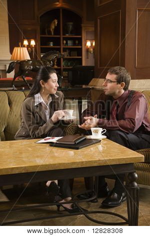 Caucasian mid adult businessman and woman drinking coffee and conversing.