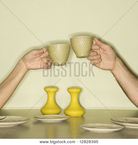 Caucasian mid-adult male and female hands toasting with coffee cups across retro kitchen table setting.