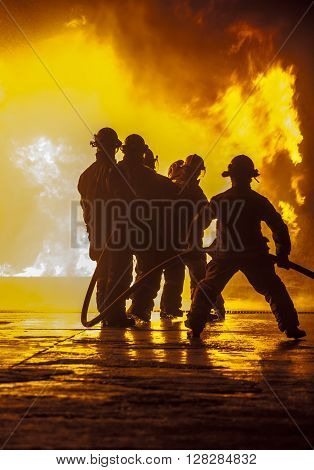 A fire fighter bracing during fire fighting