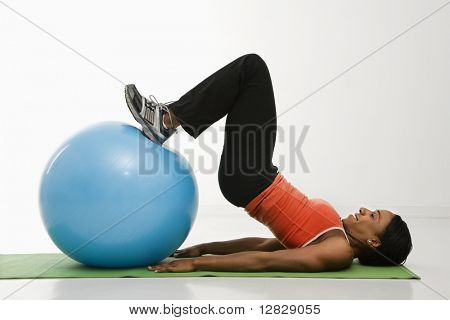 Profile of African American woman stretching on mat with feet on exercise ball.