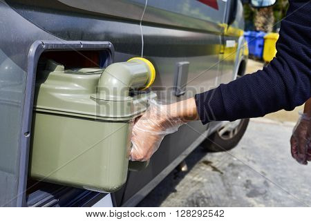 closeup of a young man removing the sewage tank of a campervan