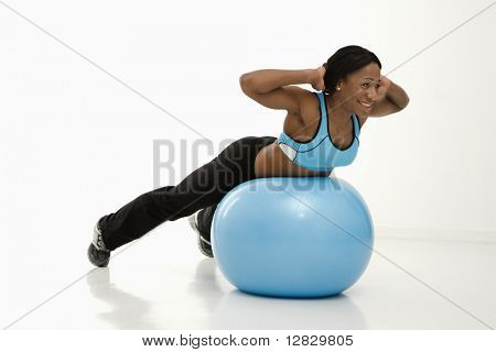 African American young adult woman working out with exercise ball.
