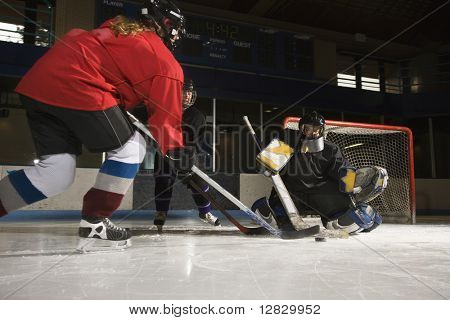 Caucasian female hockey player trying to make goal as goalie protects the net.