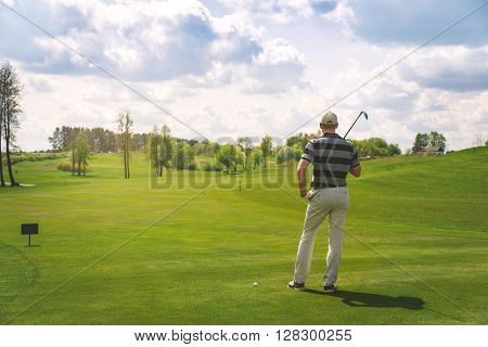 male golfer standing at fairway on golf course, back view