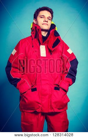 Firefighter in waterproof clothing. Studio shot on blue.