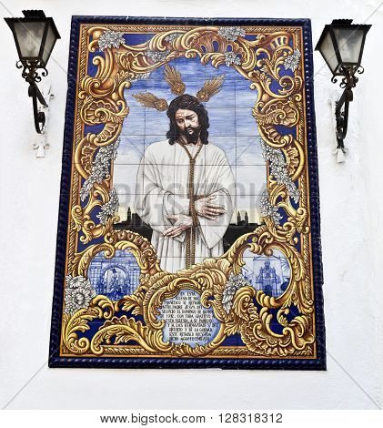 CORDOBA, SPAIN - September 11, 2015: An azulejo (tiles) ceramic panel depicting Jesus Christ on a wall in the Compas de San Francisco Cordoba on September 11, 2015 in Cordoba, Spain
